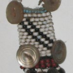 A tiny Xhosa beaded amulet holder about 1 1/2 inches or 3 cm tall  is embellished with a mother of peal button at each corner.