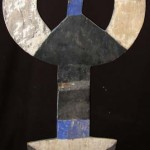 An old and well used (circa 1950) Bedu vertical plank mask. Dimensions: Length  65  inches /165 cm. This mask appears to have been  either village-repaired or made  in two pieces joined by nailing a strip of salvaged metal packing case strapping acccross the vertical section in the centre.  Three  other cracks in this old mask have also been repaired with scraps of metal strapping. This mask is for sale at http://tribalartbrokers.net/details.asp?itemId=BEB